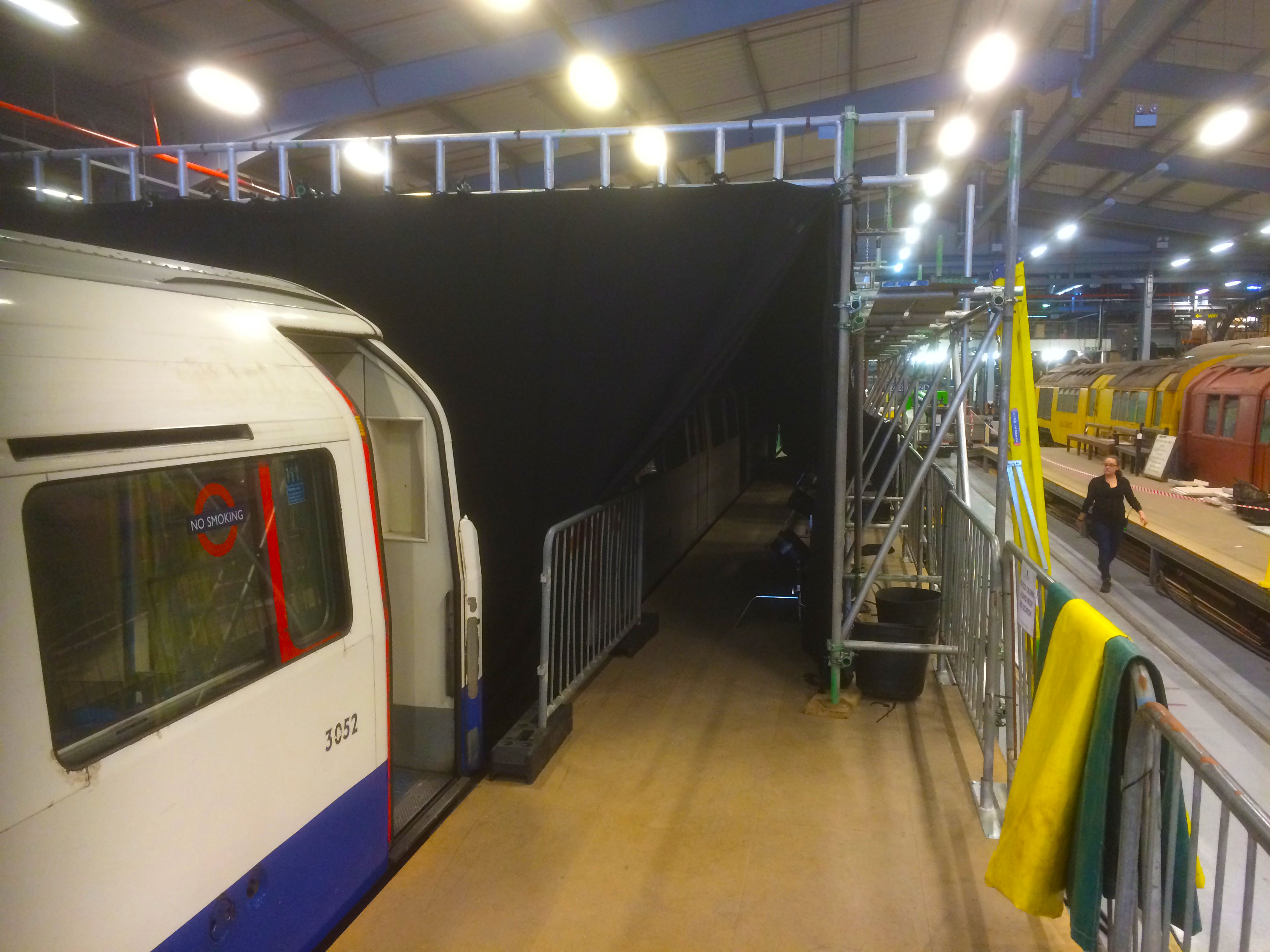 Setup of trusses in a warehouse, with a train modelling the underground tube station, and another train in the background.
