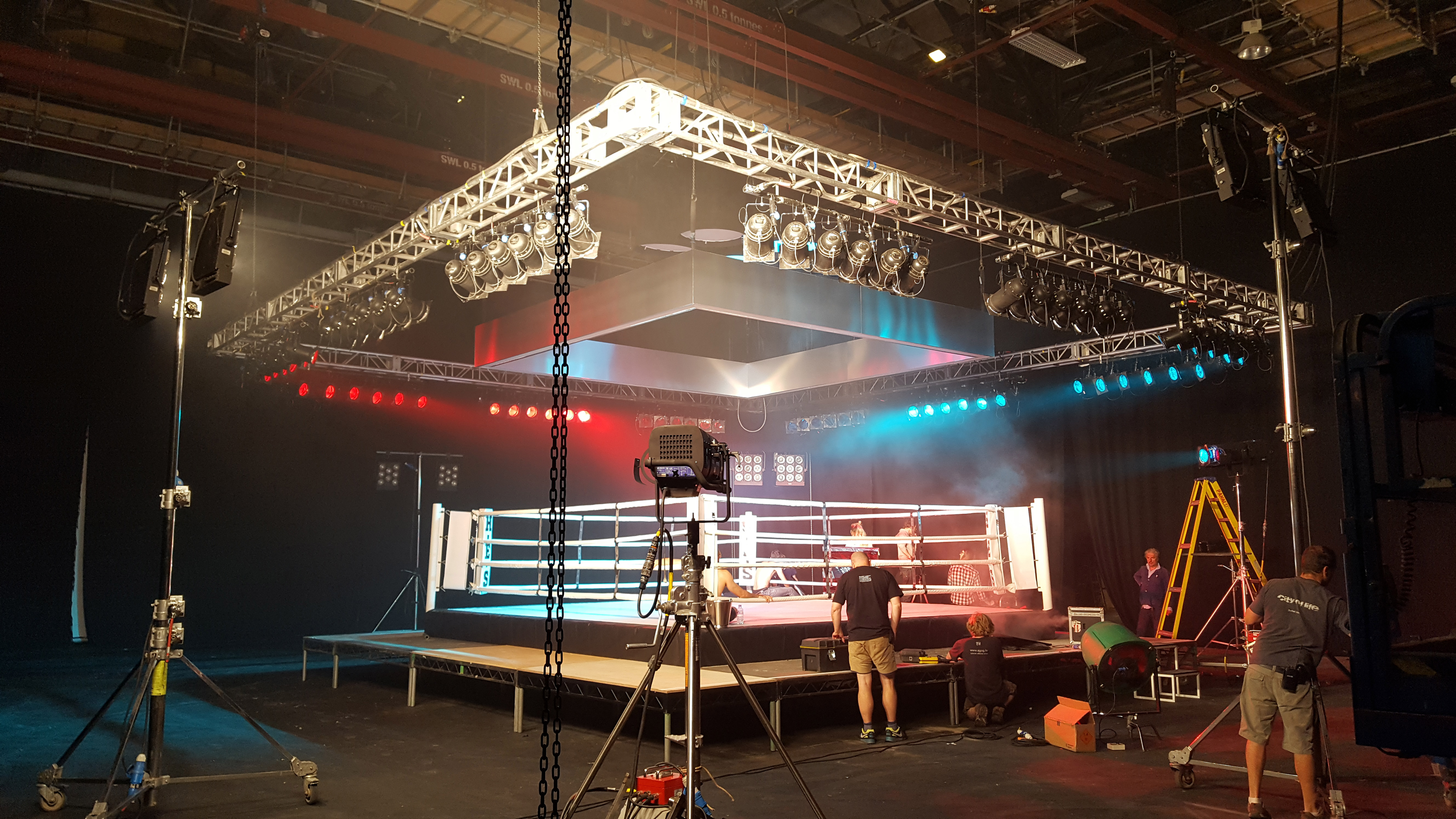 Side view of the stage lighting pipe grids set up above a boxing ring stage with red and blue spotlights.