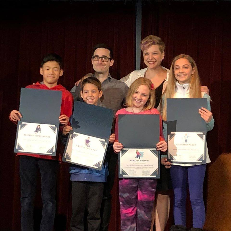 Annie and Brian standing behind two boys and two girls in their Magic Performance Program. The students are holding their certificates.
