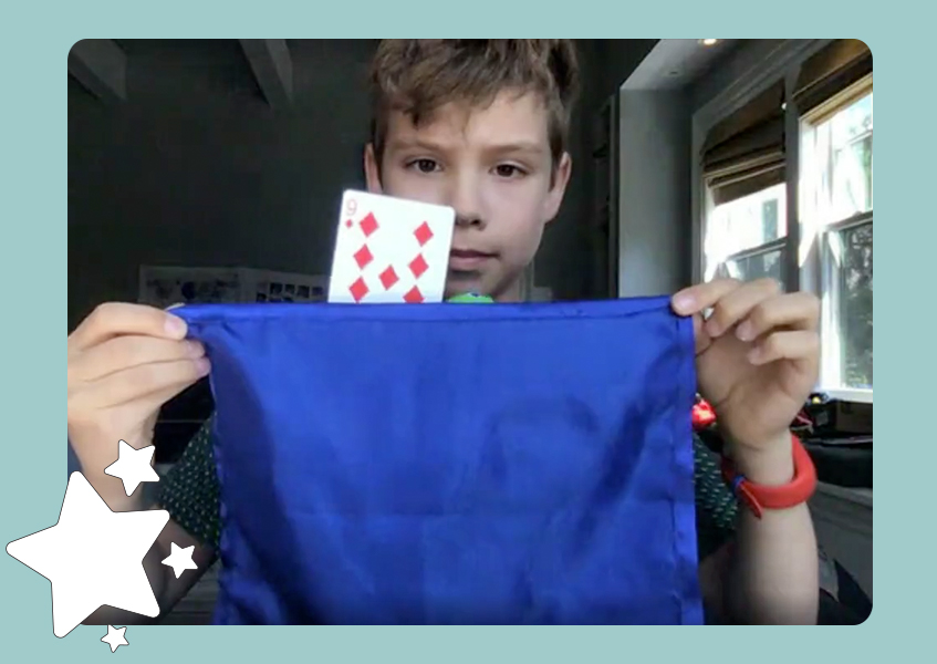 A boy holding a blue handkerchief with a floating card behind it.