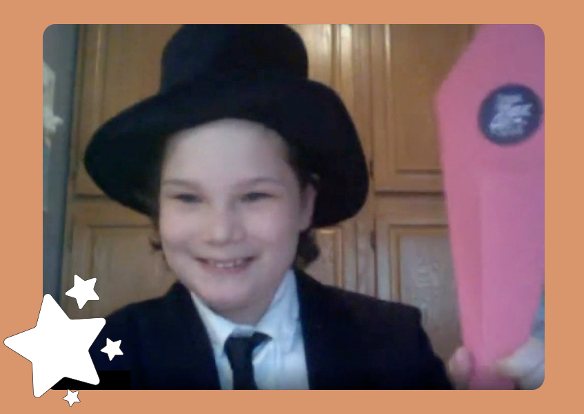 A smiling boy in a black suit and tie with a top hat holding a pink paper cone.