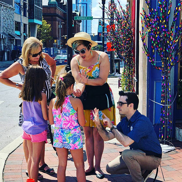Annie and Brian on a street corner teaching magic to two girls and their mother.