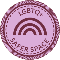 """A pink circular badge with a rainbow in the middle and words that say """"LGBTQ+ Safer Space"""""""