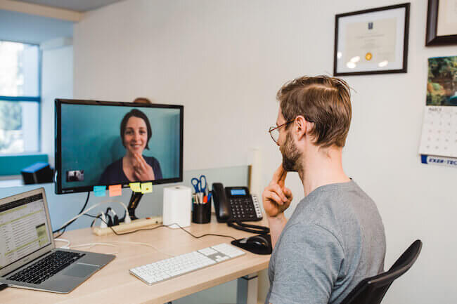 A client in their home office on a ergonomics video session with a kinesiologist