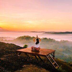 yoga pose above clouds in early morning yellow sun light and dew