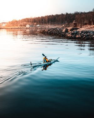 man having adventure kayaking on clear blue water at dusk