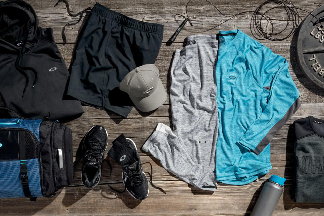 A laydown photo of Oakley training and workout gear on a wooden floor.