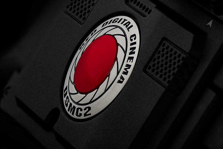 A macro image of the RED DSMC2 camera focusing on the coin logo.
