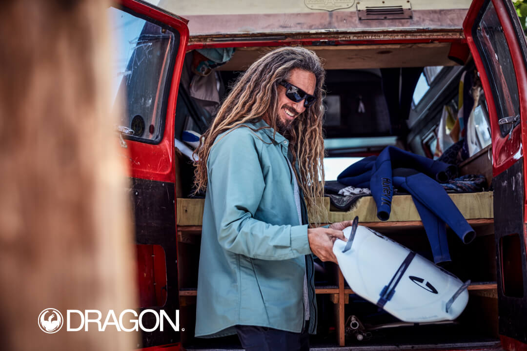 An advertisement of Rob Machado loading a surfboard into his van for Dragon Optical.