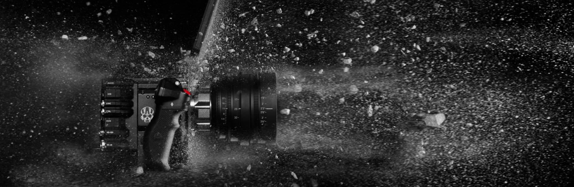 Red Digital Cinema's advertising of a camera and lens being blasted by dirt to show how reliable their product is in all conditions.