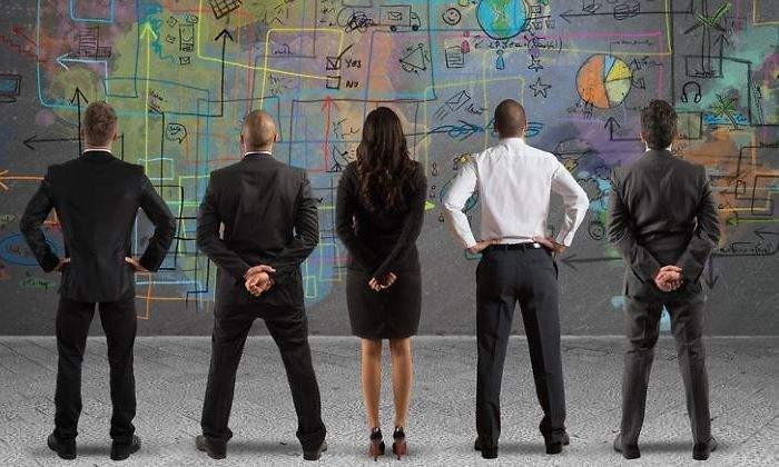 Equipe observa muro com desenhos e gráficos complexos