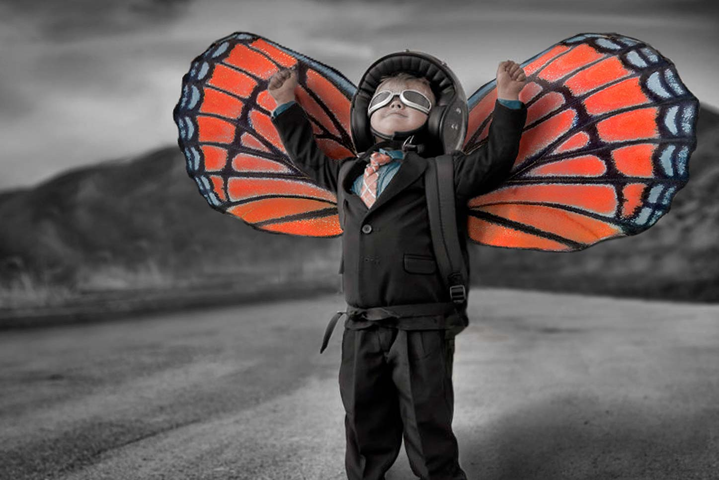 Boy in business suit about to fly with life-size butterfly wings on back.