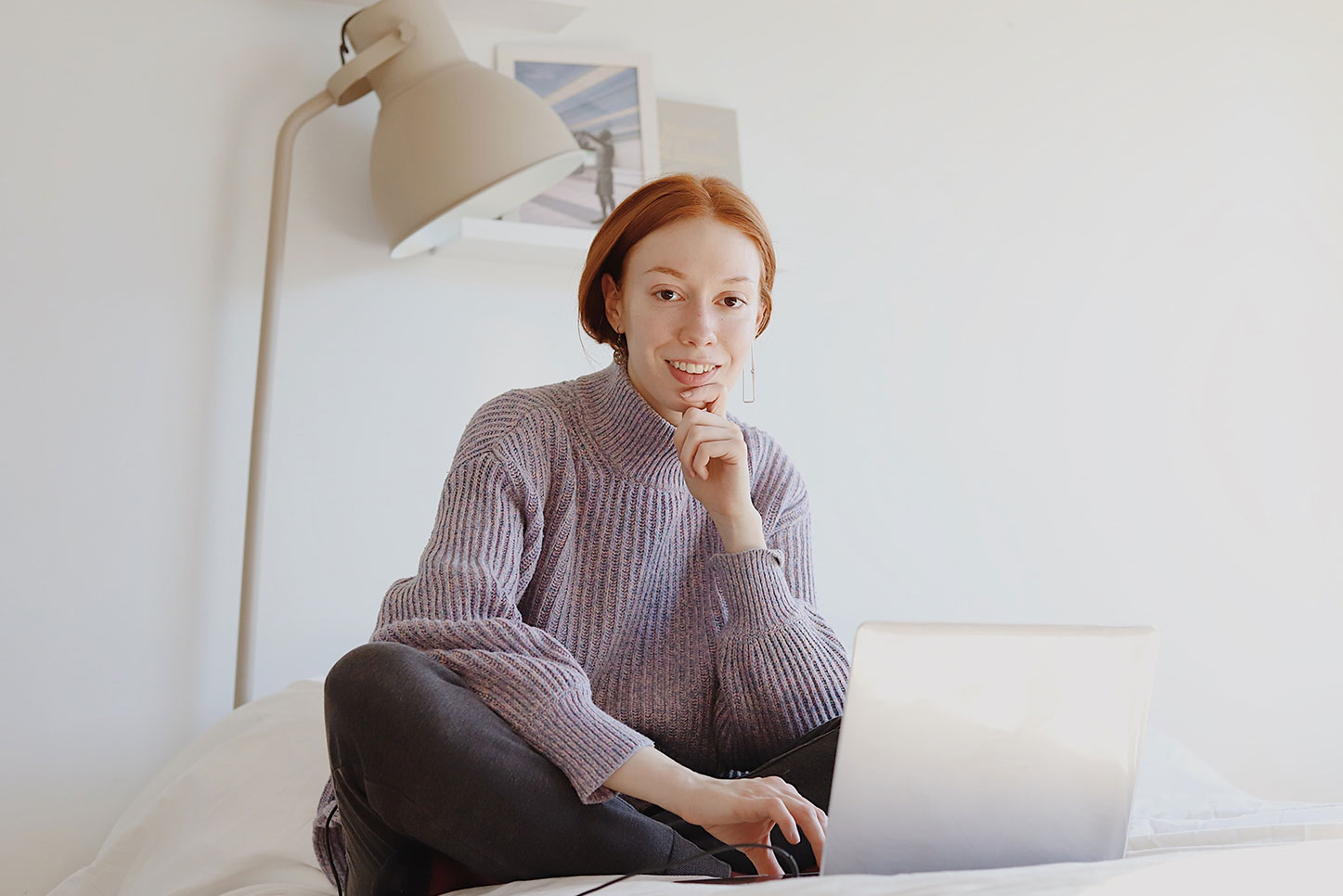 Woman sitting on bed using laptop to work.
