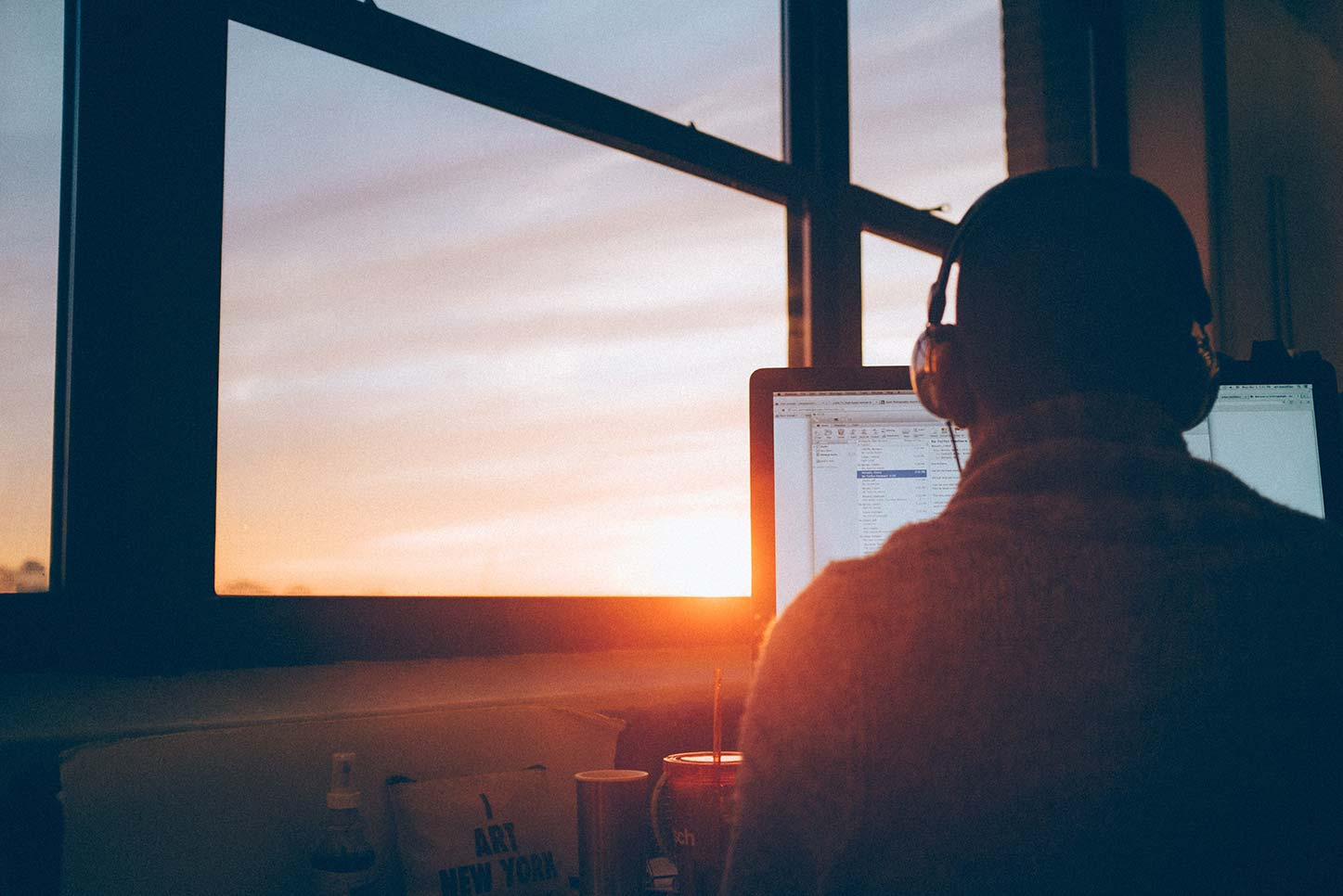 man working in front of window at sunrise