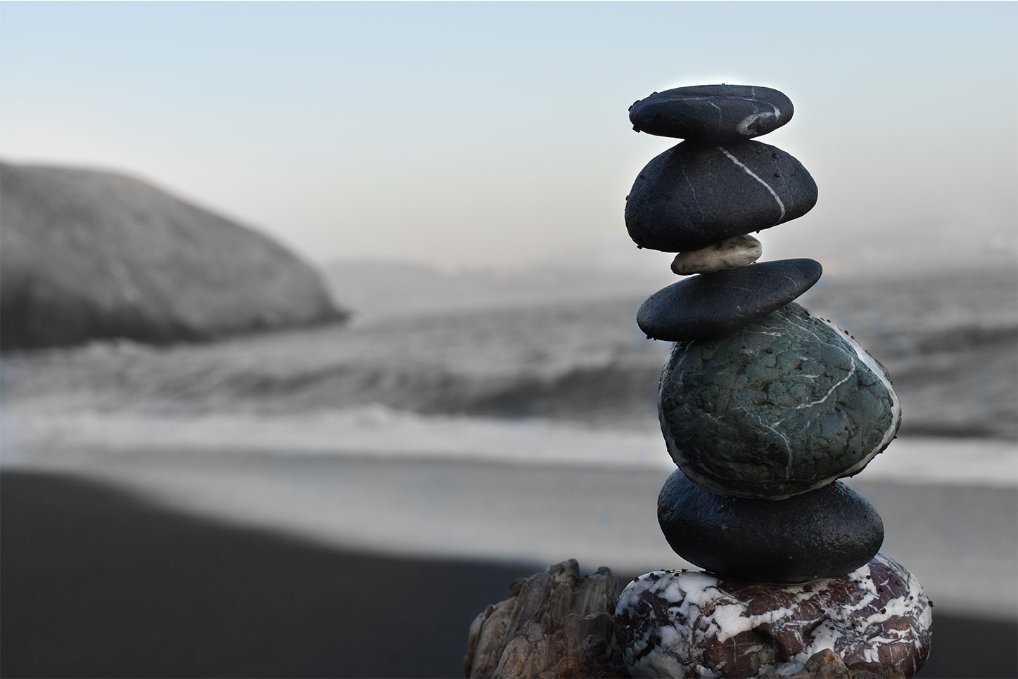 Smooth stones stacked on top of one another on a beach.