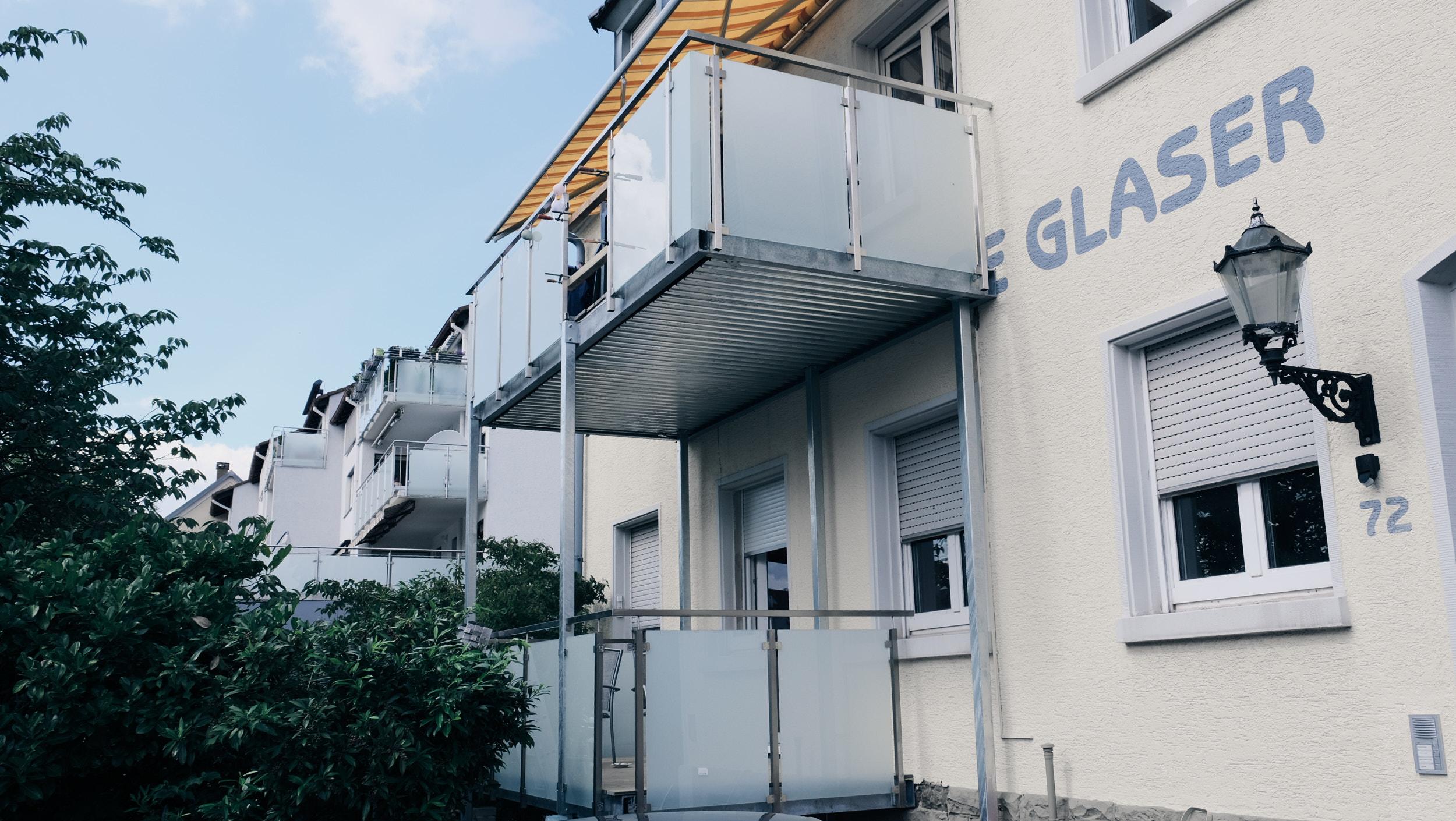 Balkon aus feuerverzinktem Stahl und Edelstahlgeländer mit Milchglasfüllung