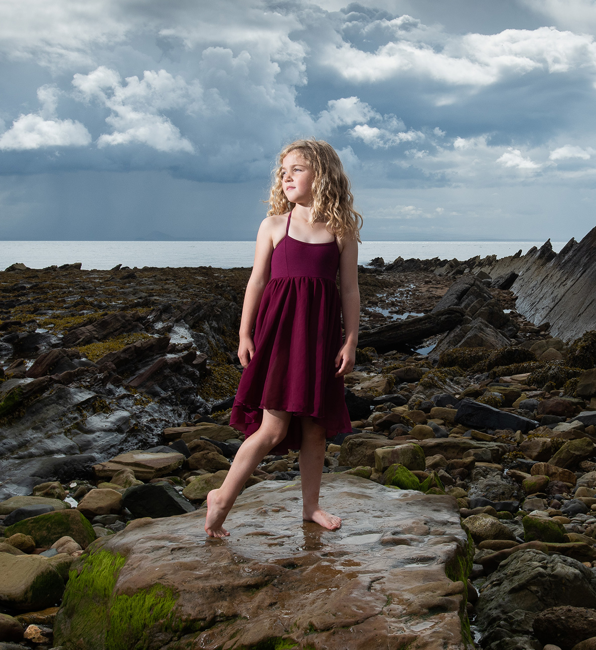 girl in maroon dress stood on rocks