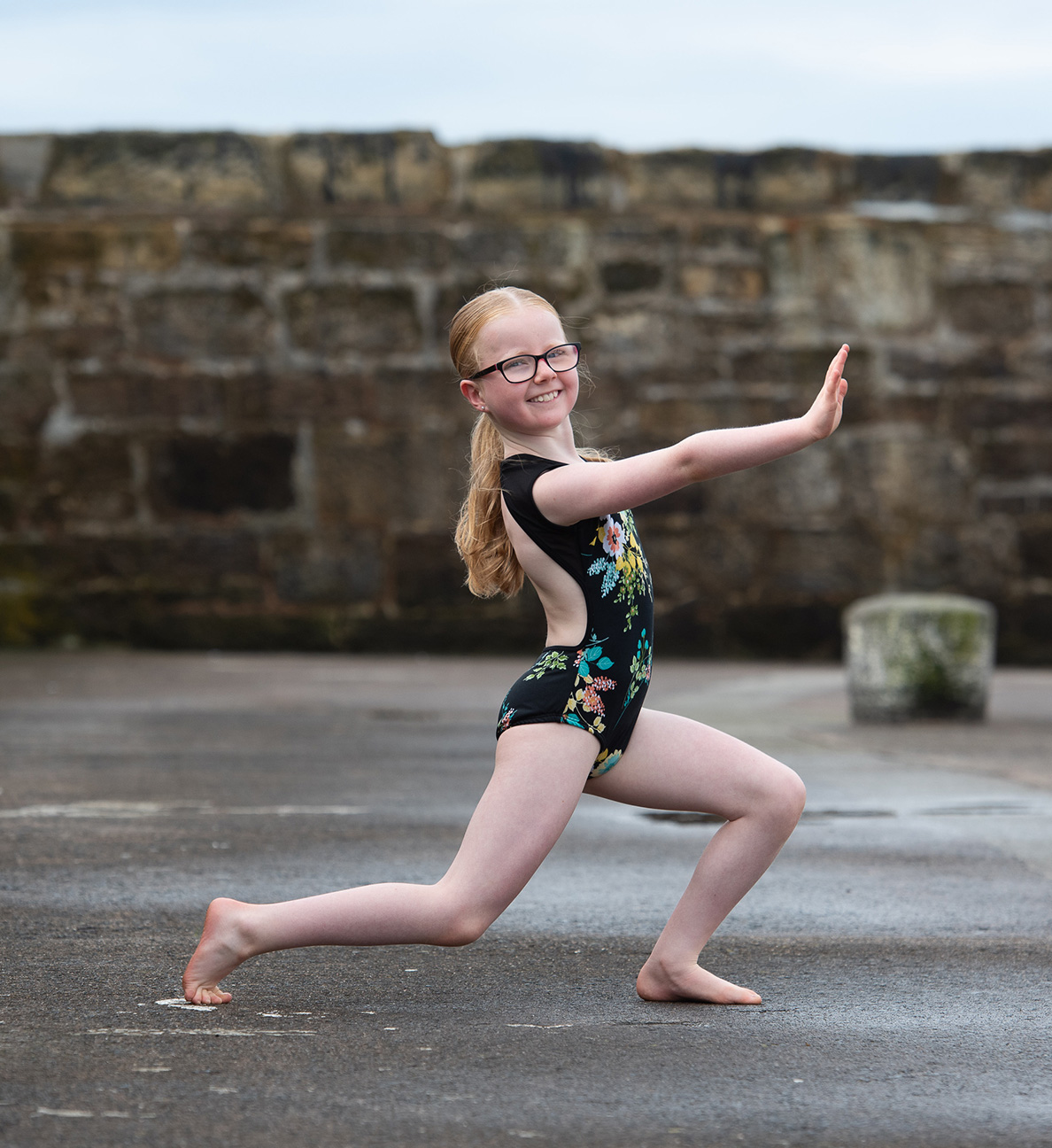 young girl in dance pose in harbour