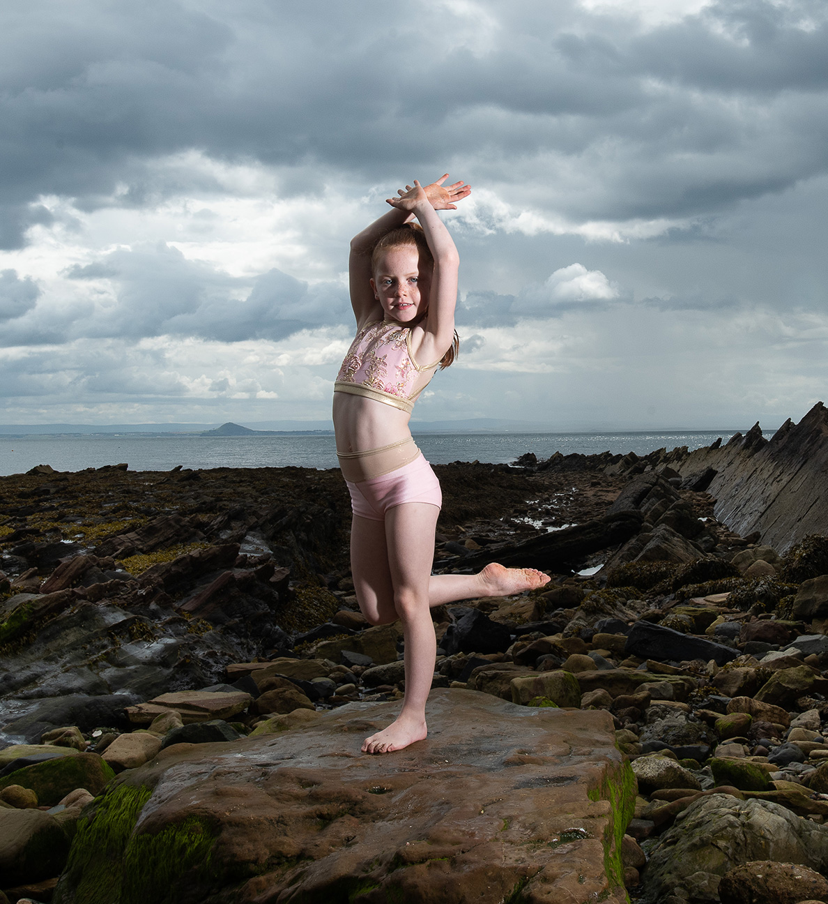 young girl in dance pose in harbour with stormy sky