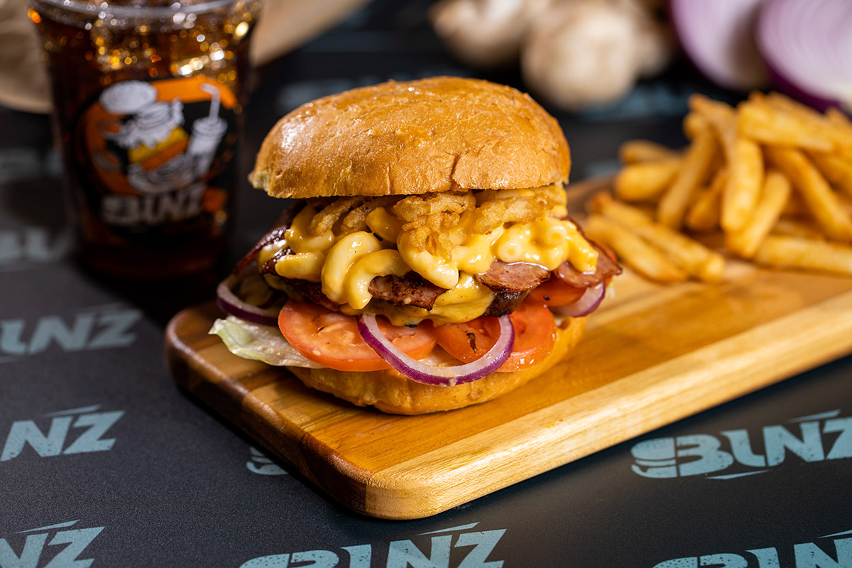 A delicious burger stuffed with mac n cheese, tomatoes, onions, and served with a side of fries!