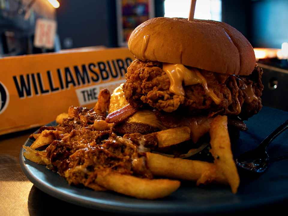 A burger on a plate with loaded fries and a Williamsburg menu in the background