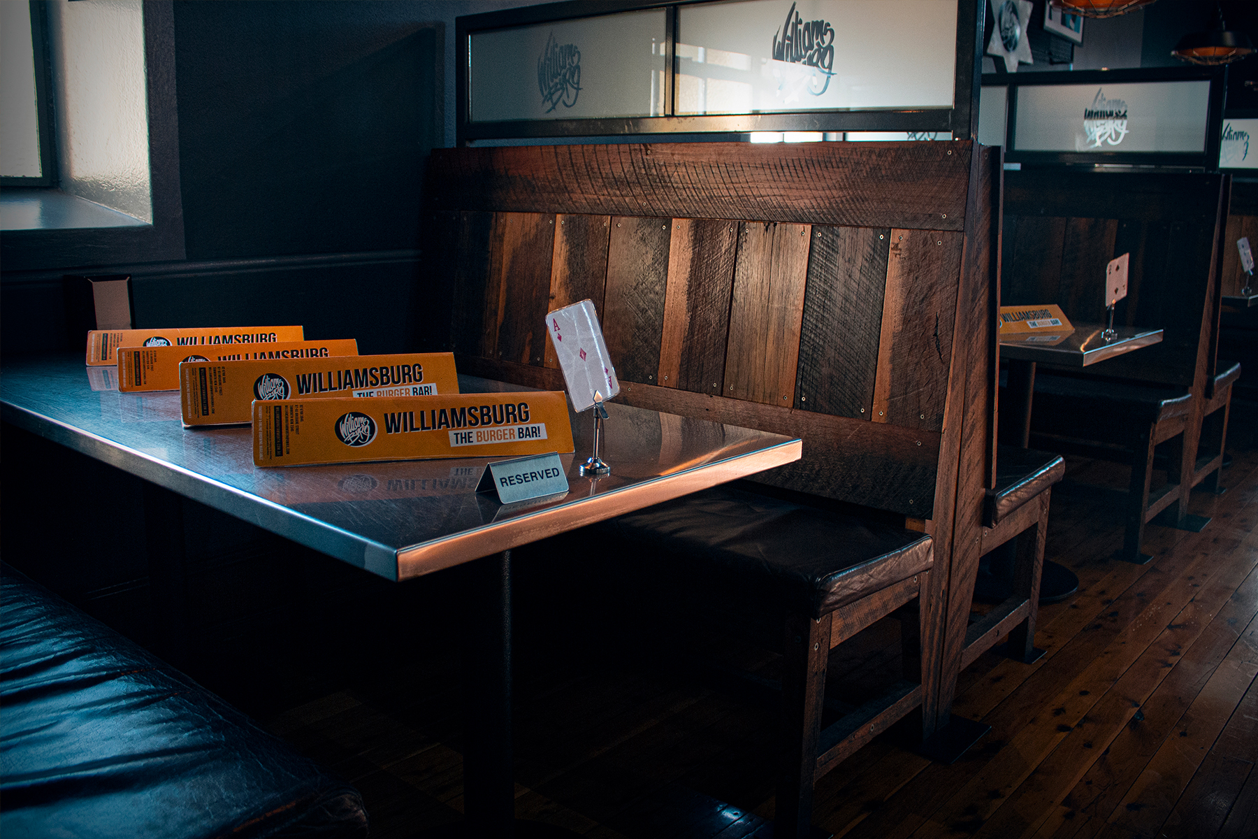 An empty booth at Williamsburg with some menus and a sign that reads reserved.