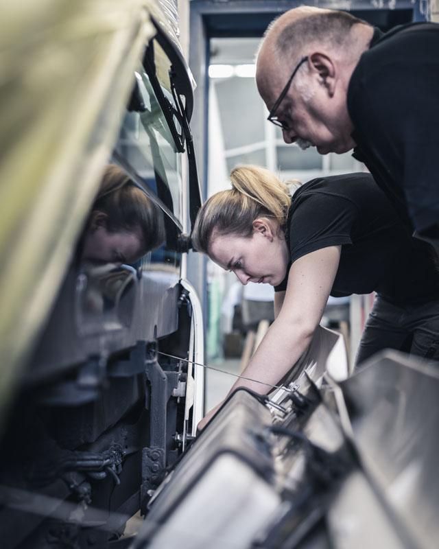 Auszubildene schraubt unter Aufsicht an einem Bus bei geöffneter Abdeckung des Motors