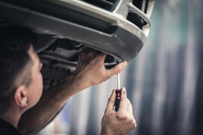 Mechaniker schraubt die Stoßstange am PKW fest