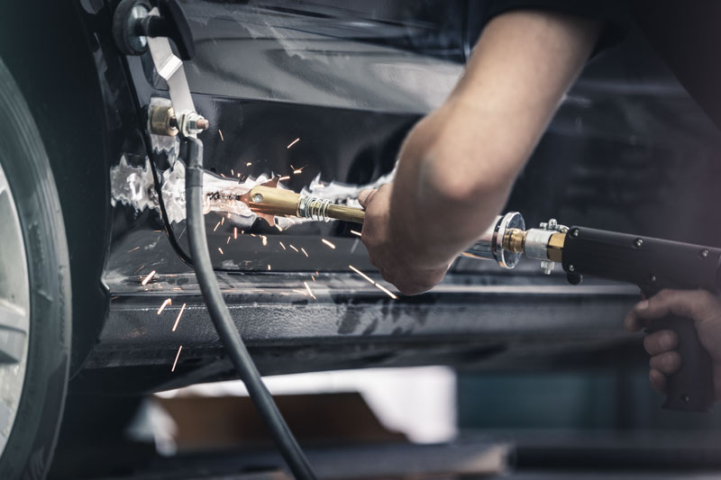Mitarbeiter bei der Beseitigung einer Delle am PKW, funken sprühen