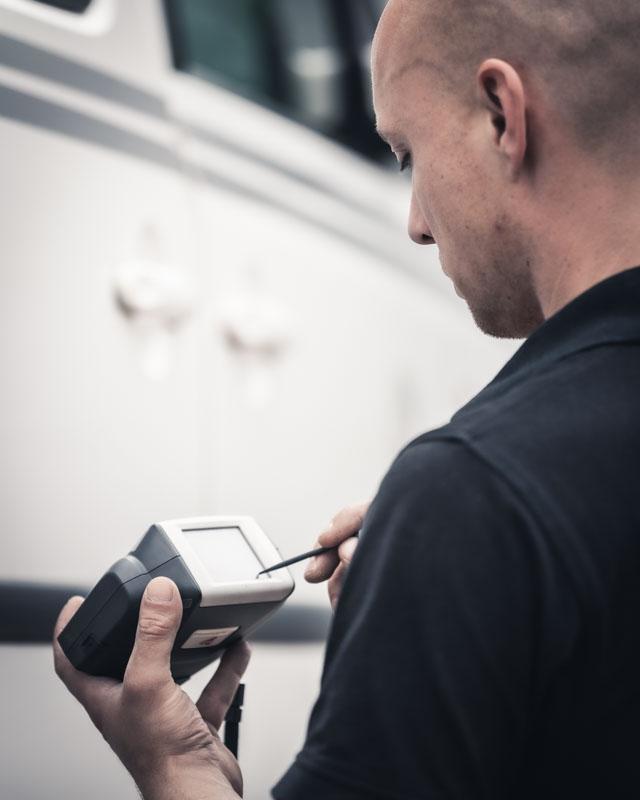 Mitarbeiter liest Farbcode eines PKW aus seinem Messgerät