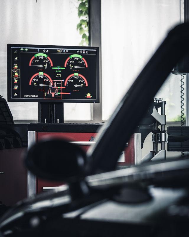 Auto auf der Hebebühne, der Monitor zeigt die Messdaten einer Achsvermessung