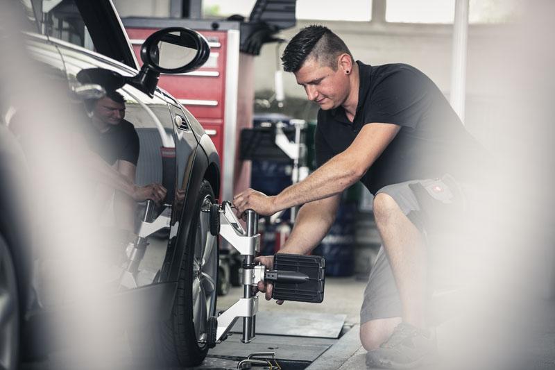 Mitarbeiter bei der Achsvermessung eines Autos auf der Hebebühne