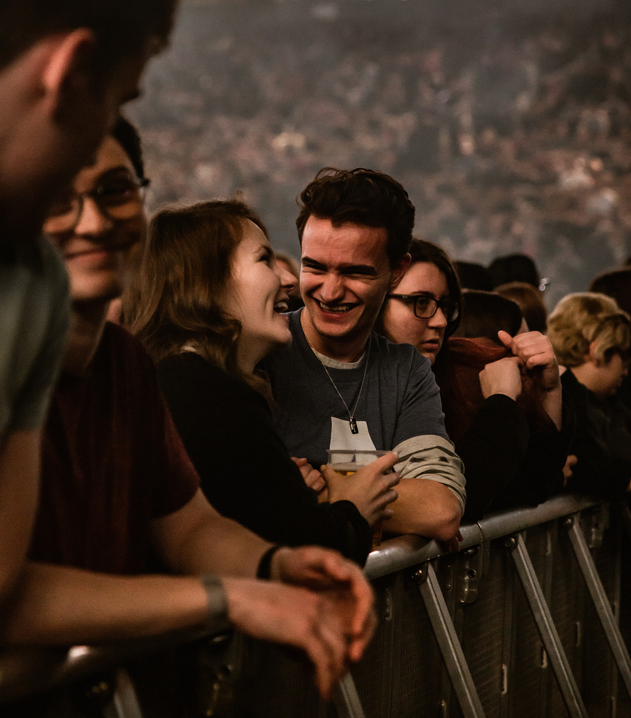 friends smiling and talking in the middle of the crowd
