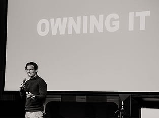 """Brant garvey speaking with a powerpoint slide behind him with the text saying """"Owning it""""."""