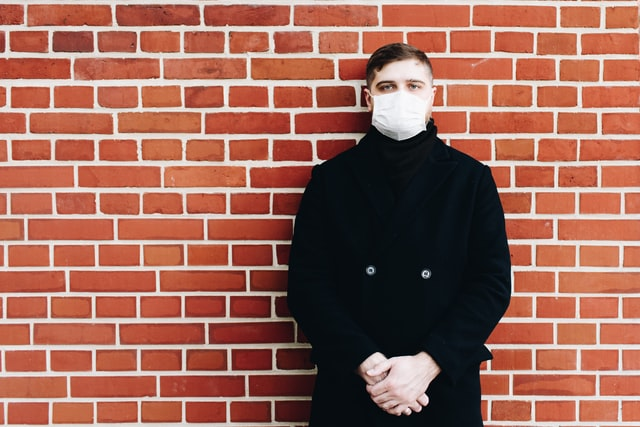 Man socially distancing with a mask on his face.