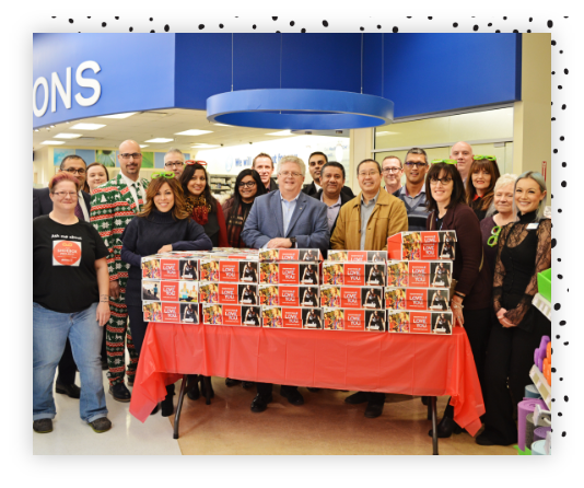 A group of employees at Shoppers Drug Mart standing in front of a desk with branded gift boxes.