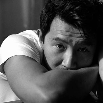 Simu Liu resting his face on his arm.
