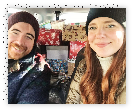 Woman and man sitting in a car with gift boxes.