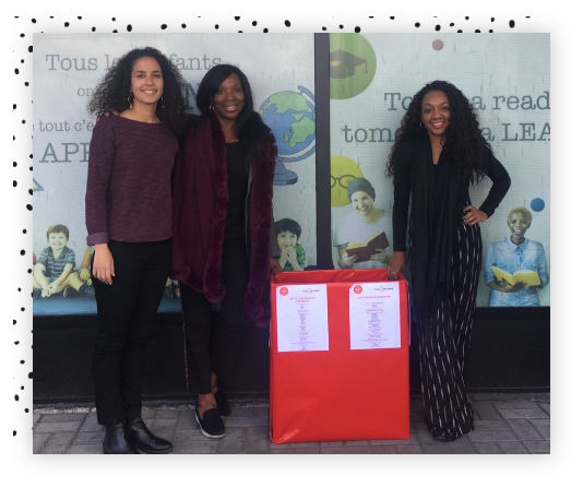 Three women standing in front of a gift drive box.