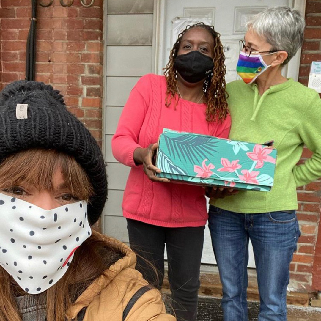 Woman taking a selfie with two women behind her holding a Shoebox gift