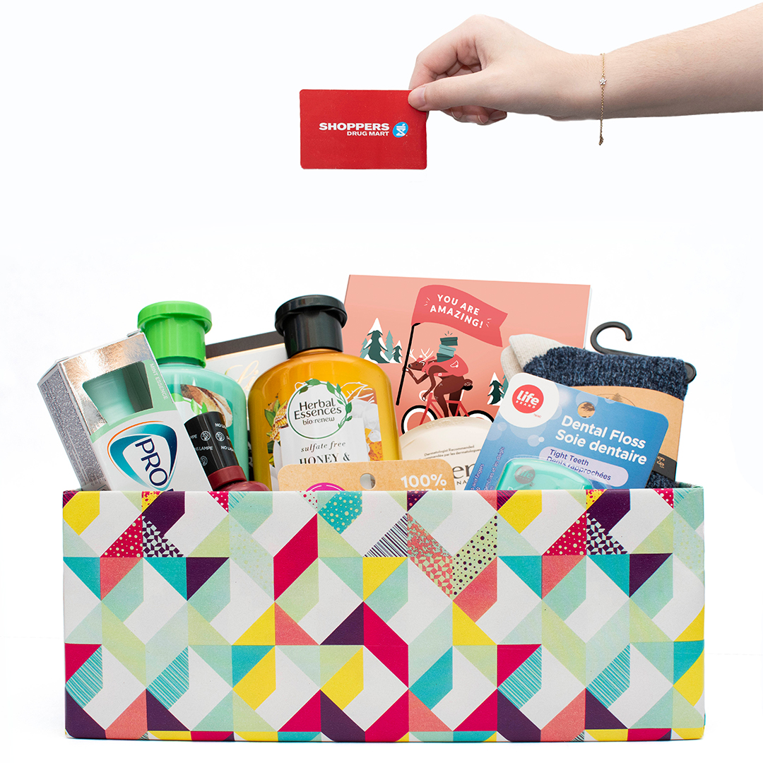 Hand placing gift items into a decorated Shoebox