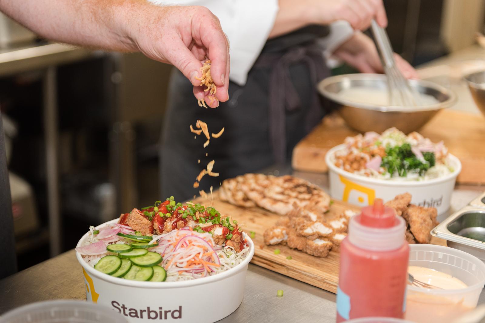 Sprinkling fresh ingredients in a Starbird Bowls