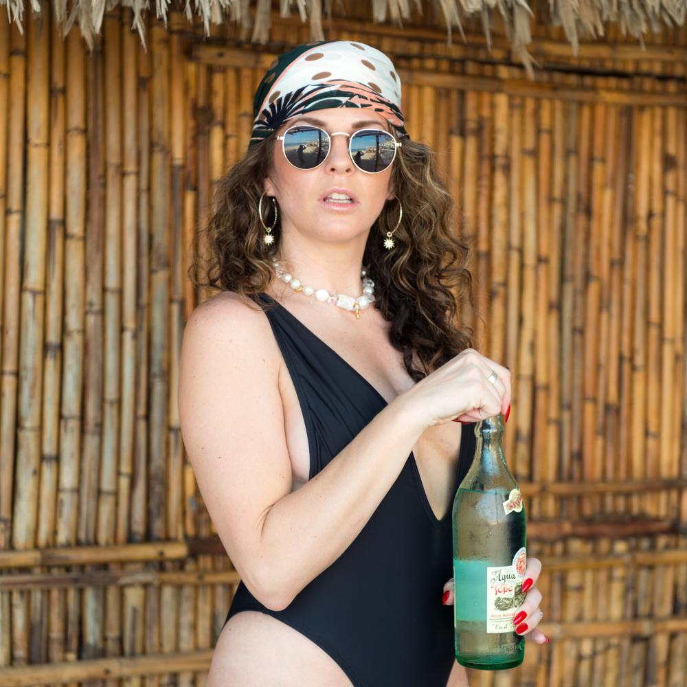 Women in One piece sun bathing suit drinking glass bottled water