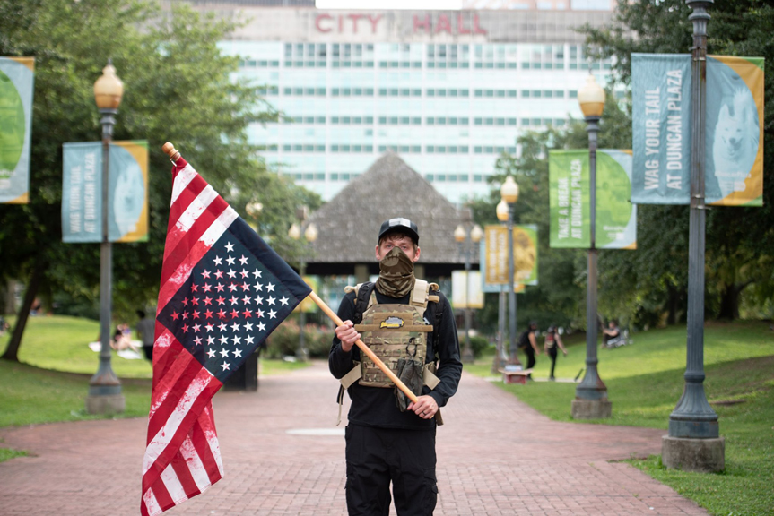 Duncan Lemp stands in Duncan Plaza in New Orleans holding a distressed blood stained flag, a signal of major upheaval in America