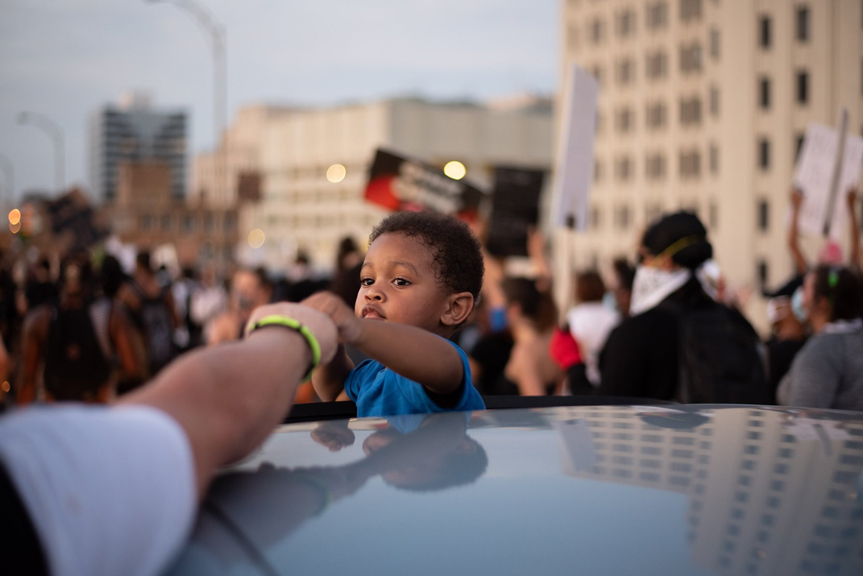 A young boy fist bumps hundreds of protesters who successfully took over Interstate 10 in New Orleans. Many of the commuters happily joined the moving protest at times leaving their vehicles in solidarity with demonstrators.