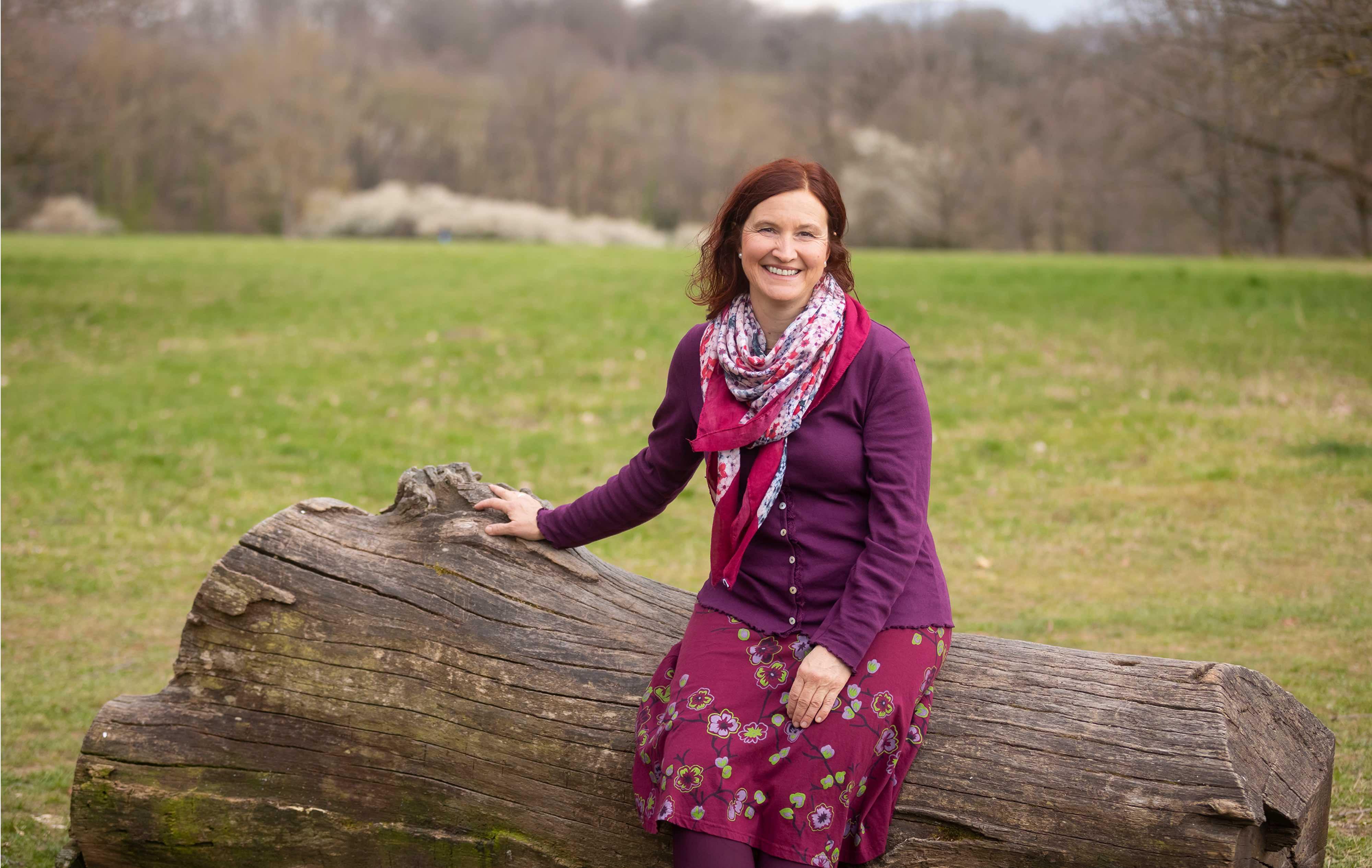Christine sitzt auf einem Baumstamm