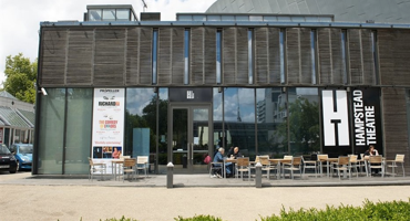 Two people sitting on chairs outside the Hampstead Theatre.