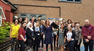 Multi cultural staff members standing outside Holy Trinity School for a group photo.