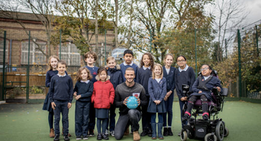 Group photo of pupils and David Beckham when he visited Church of England primary school in Kentish Town.