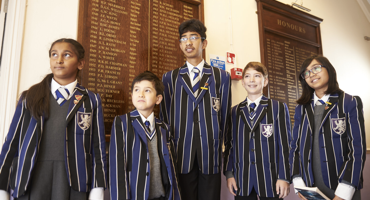 Group of children aged 3 to 11 standing in front of the leader board at Hendon Prep.